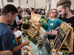 A visitor looks over a display of soy candles