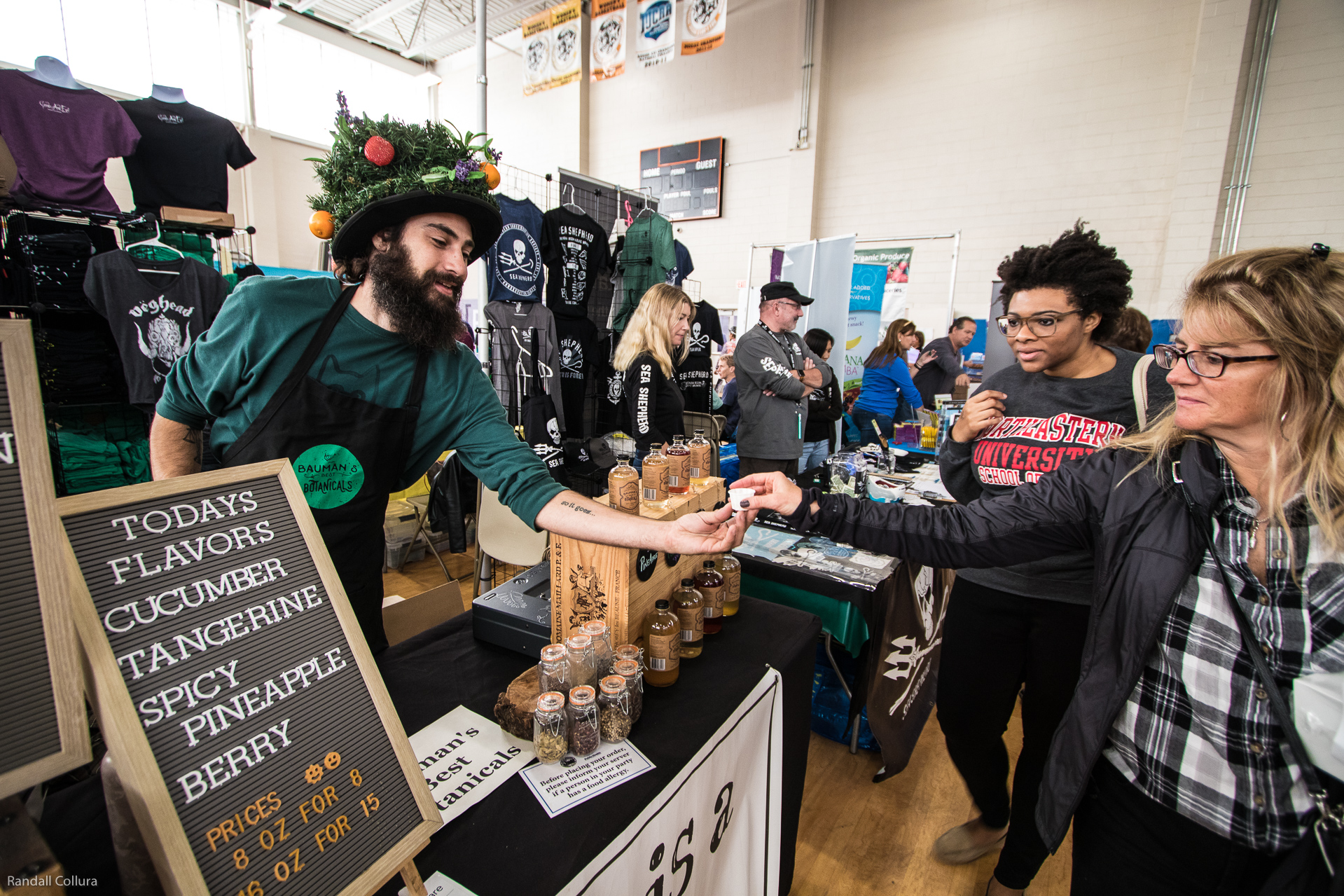 Man wearing a fun hat with costume veggies on it serves a food sample to a woman