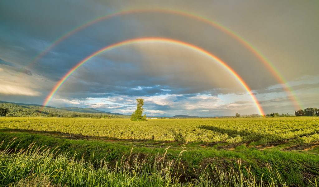 double rainbow over a farm