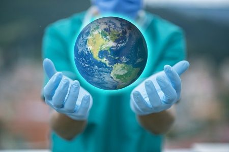 a person wearing surgical gloves holds a globe