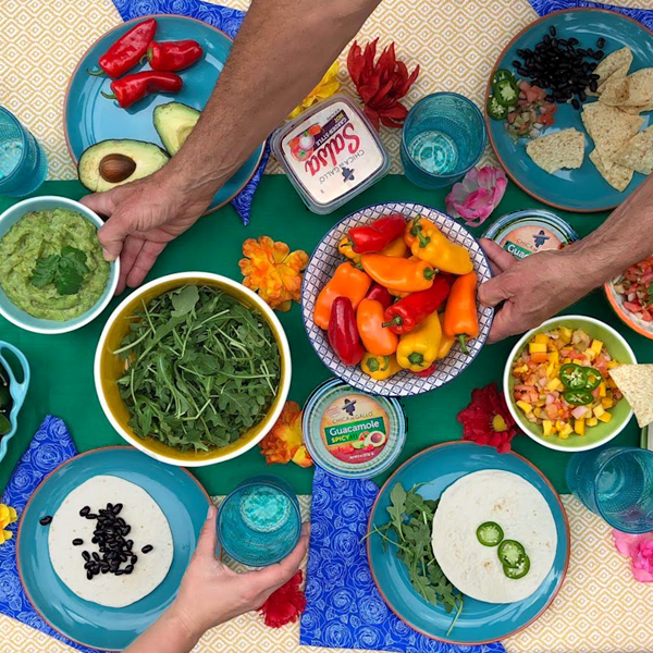 colorful veggie dips, guacamole, and hot peppers